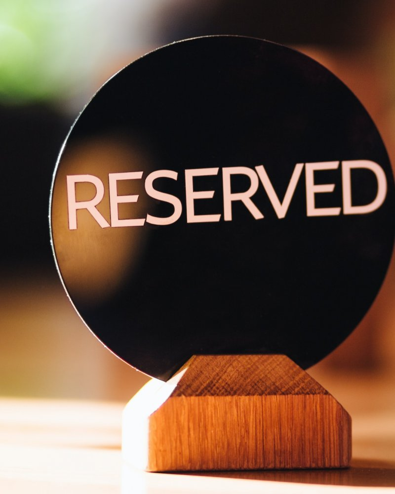 Reserved sig on wooden table in cafe, denotes that this place is occupied